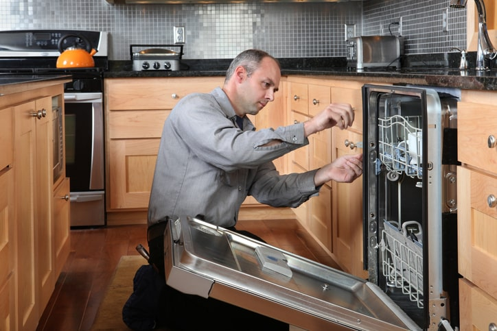 Worker repairing energy efficient dishwasher in beautiful, contemporary kitchen.